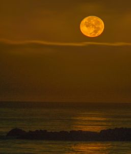 harvest-moon-setting-over-ocean-by-paul-brewer